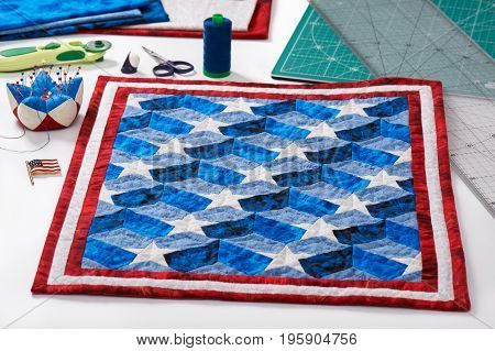 Completed quilt with stylized elements of American flag patchwork tools