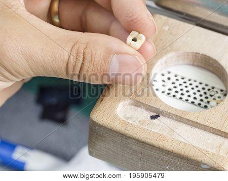 Dental Technician Presenting A Tooth, A Dental Implant In A Dental Lab.