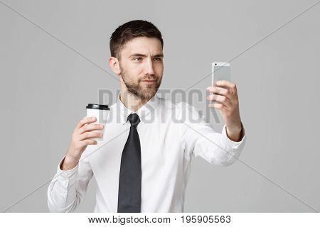 Lifestyle and Business Concept - Portrait of a handsome businessman enjoy taking a selfie with take away cup of coffee. Isolated White background. Copy Space.