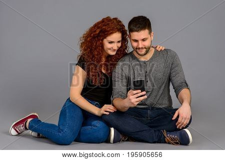 A beautiful young couple sitting on the ground and looking at a smartphone and smiling
