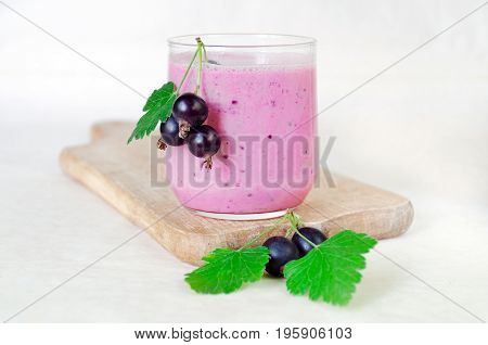 Milk cocktail of black currant berries and oat flakes in a glass cup on a wooden board. Decorated with black currant berries. light background. side view
