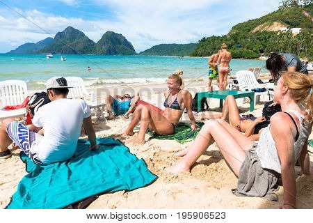 EL NIDO PALAWAN PHILIPPINES - JANUARY 18 2017: Foreigners relaxing and getting tan at Las Cabanas Beach during a hot day in El Nido.
