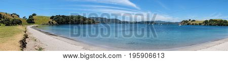 Panorama of empty beach on Urupukapuka Island in summer in Bay of Islands New Zealand NZ with boats anchored