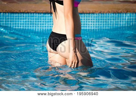 Girl in a swimsuit in the pool .