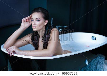 Sexy caucasian woman taking bath at modern bathroom.