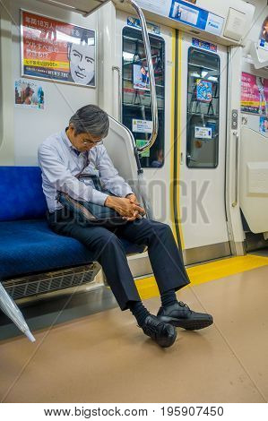 HAKONE, JAPAN - JULY 02, 2017: Unidentified man sleeping at the interior of train during rainy and cloudy day.