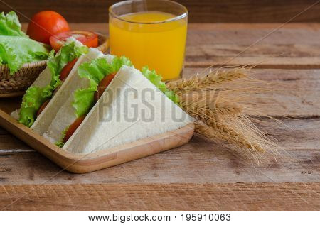 Triangle slice piece of sandwich ham cheese with lettuce and tomato on wood plate. Homemade sandwich served with orange juice for breakfast or lunch. Delicious ham cheese sandwich ready to served on wood table with fresh orange juice