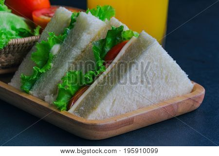 Triangle slice piece of sandwich ham cheese with lettuce and tomato on wood plate. Homemade sandwich served with orange juice for breakfast or lunch. Delicious ham cheese sandwich ready to served on granite table with fresh orange juice
