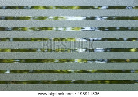 full frame abstract blue green lined translucent plastic foil in front of vegetation background