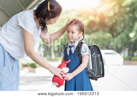 Mother standing at school holding hands and teaching her daughter love concept