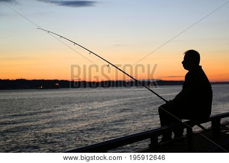 NEW YORK - JULY 15, 2017: Fisherman silhouette at sunset near Verrazano Bridge in New York Harbor