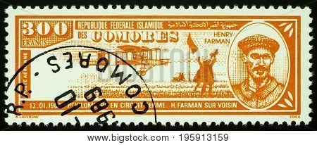 Moscow Russia - July 18 2017: A stamp printed in Comoros shows French aviator Henri Farman and old airplane Voisin (1908) series
