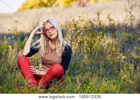 Young attractive blonde posing and sitting in autumn grass