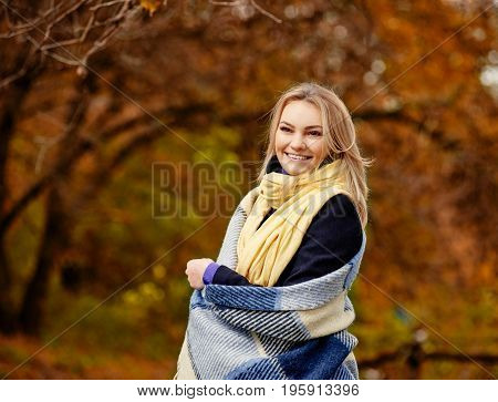 Smiling blonde woman covered in plaid in autumn forest