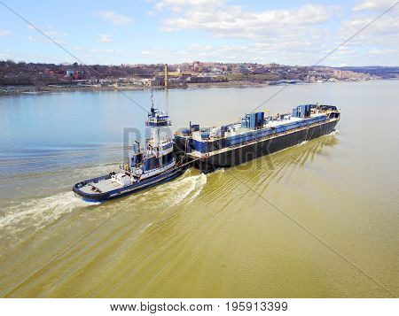 Ship pushing a tanker on the river
