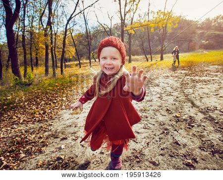 Portrait of cute happy girl having fun in autumn park