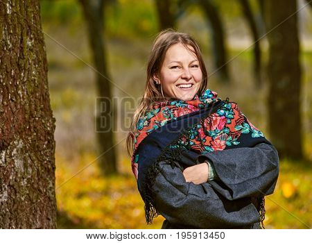 Cheerful woman posing in autumn park with crossed hands