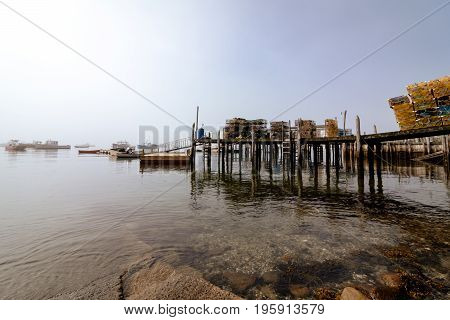 Lobster traps sit on the dock as the morning fog fades