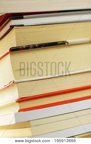 A stack of various books closeup photo