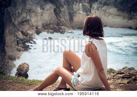 Freedom young caucasian woman sitting and posing on mountain peak rock, cliff. Beautiful blue ocean on the background. Tropical island Nusa Lembongan, Bali, Indonesia, Asia. Rare view.