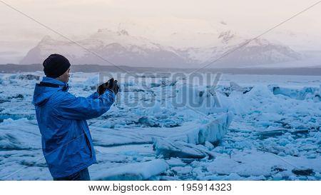 Asian Man Using Camera Taking Photo At Glacier Lagoon Iceland. Beautiful Travel Memory