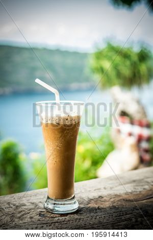 Glass Of Cold Coffee On Wood outside. Tropical island, Indonesia.