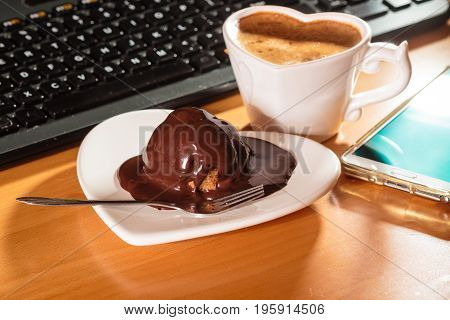 Cup Of Coffee And Chocolate Cake Next To Computer.