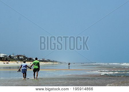 Jacksonville, Florida - May 5, 2011. Happy senior couple enjoys a romantic stroll on the beach.