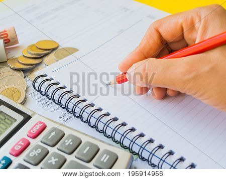 abstract money saving. Closed up woman hand using calculator with note book and red pencil in yellow and white background.