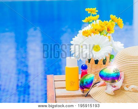 Sunglasses with summer hat sunblock / sunscreen and flowers by the swimming pool. Vacation and relaxation summer travel concept.