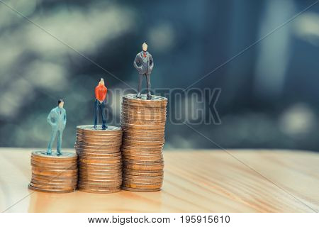 Miniature People, Small Figures Businessmen And Woman On Top Of Coins, Business Concept. Shallow Foc