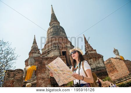 Ayutthaya tourist woman on asia travel sightseeing holding map by Wat Yai Chai Mongkhon temple. Tourism people concept with Asian chinese girl smiling happy with camera and backpack for holiday poster