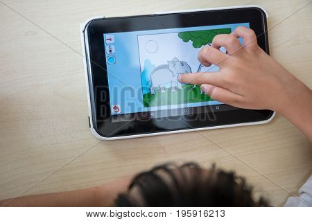 Child's hands playing tablet computer at outdoor cafe