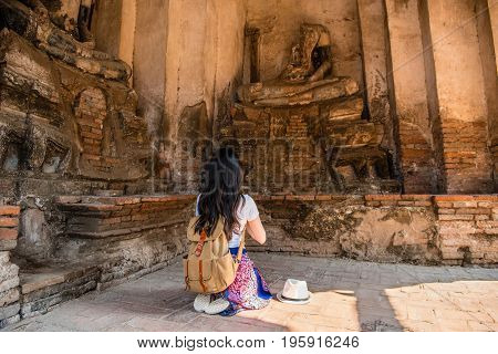 Tourist Girl Praying In Front Of  Buddha Statue
