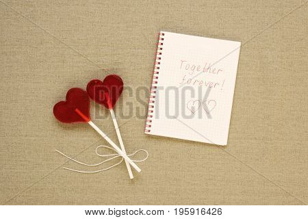 Two heart-shaped lollipops and a note with Together forever sign. St. Valentine's, copy space.