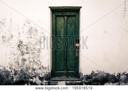 antique wooden green door have padlock and white wall