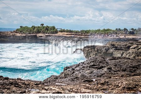 A beautiful blue wave crashes down at the rocks in Devil's Tear, tropical island Nusa Lembongan, Indonesia. Sunny day, big waves.