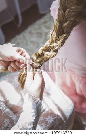 Braiding the spit of a little girl. Hairstyle, hairdresser.