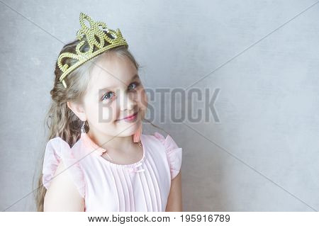 Little girl in the crown smiles. Princess, fairy. Portrait of a girl