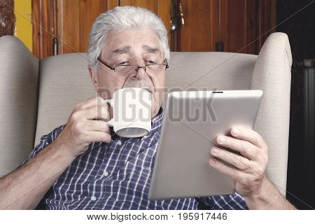 Man Drinking Coffee And Using Tablet.