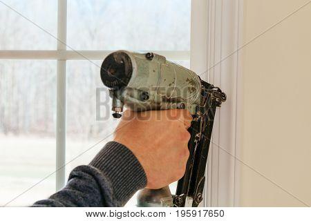 Carpenter Using Nail Gun To Moldings On Windows, Framing Trim,