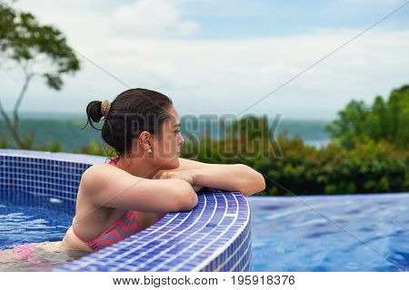 Young woman staying in outside spa pool