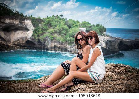Two happy young female friends sitting on the cliff, ocean on a background. Happy vacation in Indonesia. Two smiling youn women.