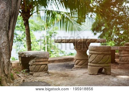 Patio with stone furniture on beach background