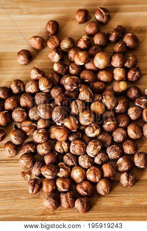Plenty of organic hazelnuts on wooden cutting board health concept