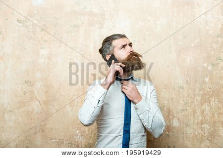 hiprter or bearded man with long beard and stylish hair on thoughtful face in tie and white shirt on beige background speaking on mobile phone conversation and information businessman