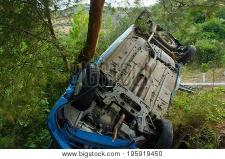 Сar accident on a mountain forest road. Turned upside-down the broken car pulled off the road and fell into a ravine. Asphalted mountain forest road
