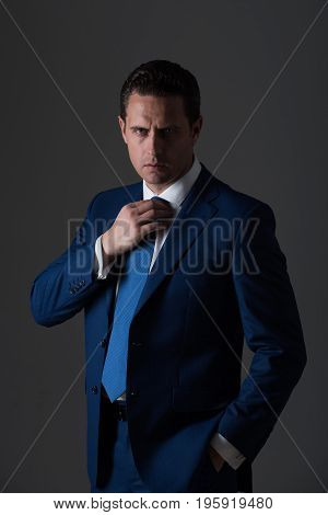 Man Adjusting Tie In Fashionable Blue Formal Suit
