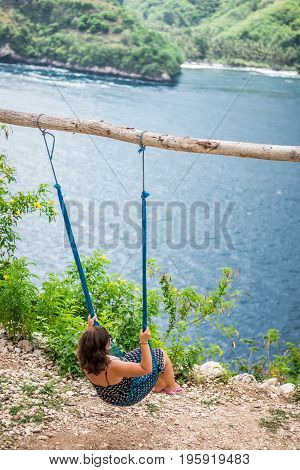 Vacation concept. Young woman swing on a beach swing on the cliff. Selective focus. Tropical island Nusa Lembongan. The ocean on a background.