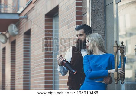 Girlfriend and boyfriend looking at bottle of wine. Pretty woman or girl in blue dress and man or hipster outdoors on brick wall. Alcohol and convive. Couple in love. Unhealthy lifestyle. Bad habits